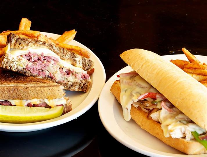 Two Entrees on plates next to each other. A corned beef and cabbage with fries and a pickle and a Cheesy Lassie/ Irish Philly Hoagie