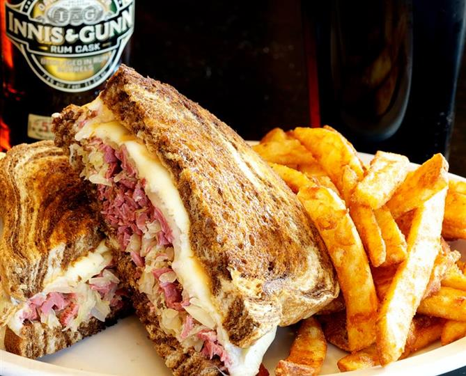 Kerry's Classic Reuben sandwich with a side of fries and a beer