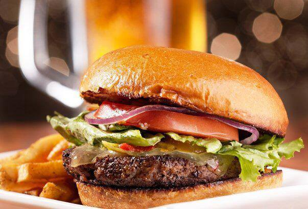 Burger with lettuce, tomato, onions, pickle on a bun with fries