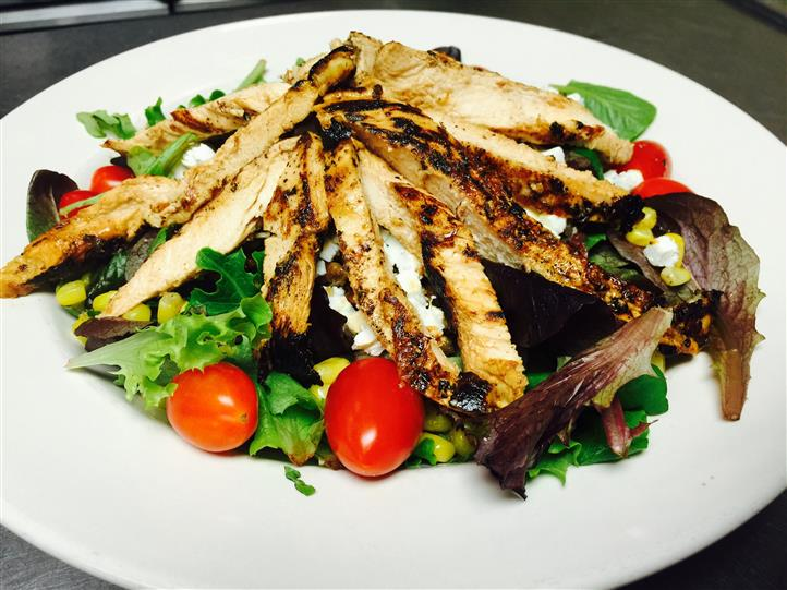 Fresh spring greens and romaine lettuce, tomatoes, red onions, and corn topped with grilled chicken