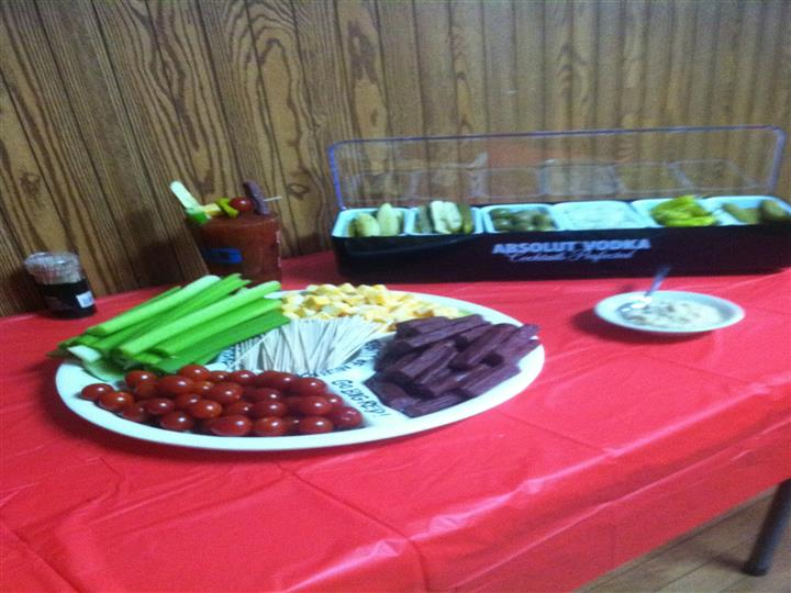 A dish with cherry tomatoes, celery, corn and beet and a case with a variety of pickles on a table with a red table cloth