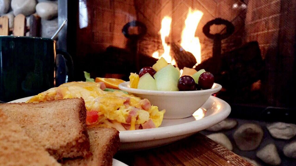 Scambled eggs on a white plate with fruit in a white bowl infront of a fireplace