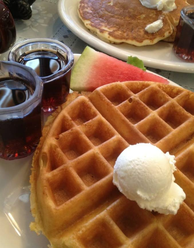 Belgian waffle with butter and a side of maple syrup and a slice of watermelon