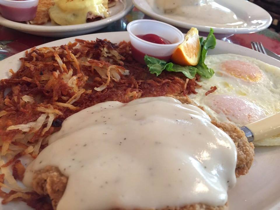 Chicken fried steak with gravy, hasbrowns and two fried eggs on a plate