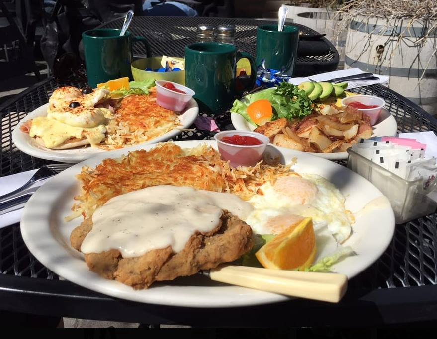 Chicken fried steak with two fried eggs and hasbrowns on a plate with two breakfast plates with assorted breakfast iems in the background