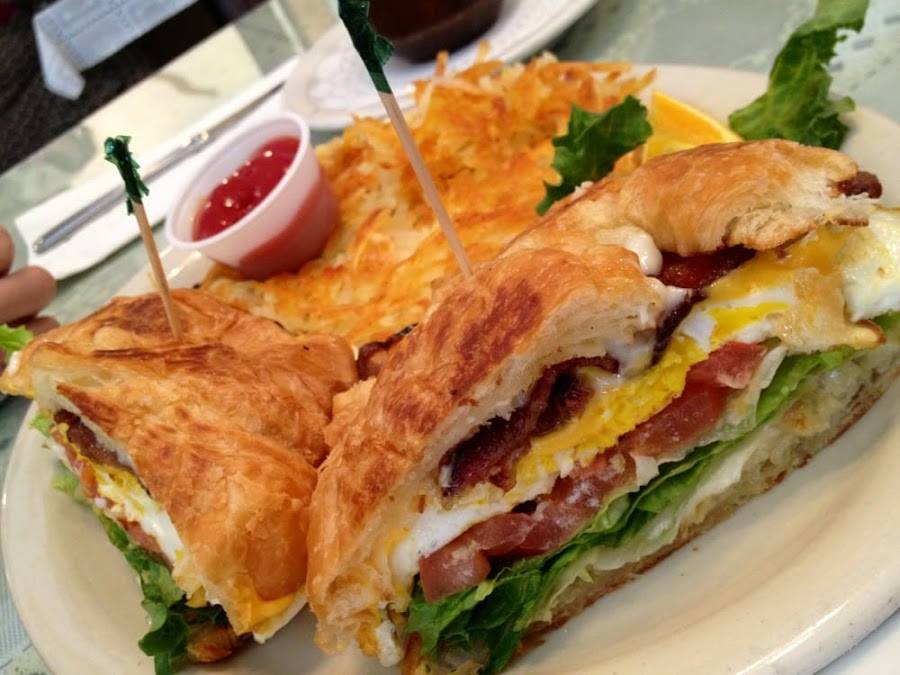 Egg sandwich on a croissant with bacon lettuce tomato and side of hashbrowns