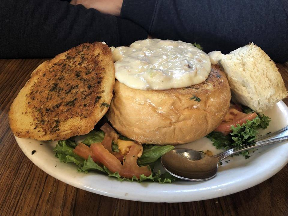 Clam chowder soup in a bread bowl over lettuce and tomato on a plate
