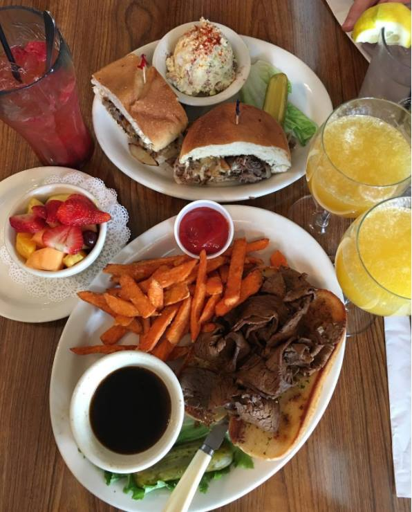 Two plates with steak sandwiches and a side of au jus, sweet potato fried and assorted drinks