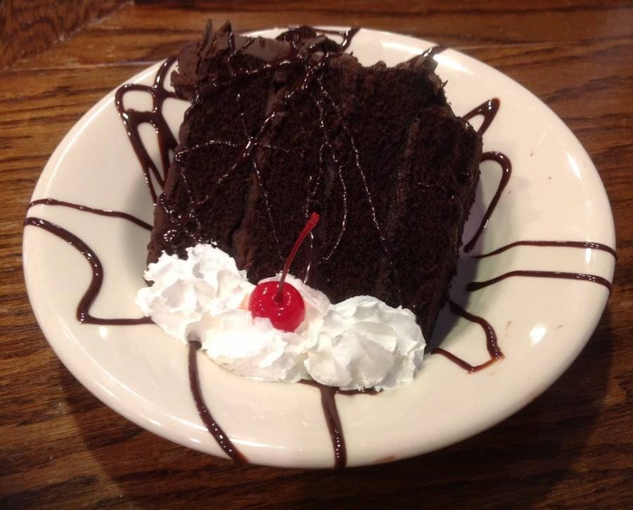 Slice of chocolate cake with whipped cream and a cherry