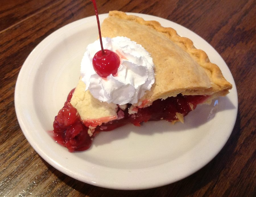 Slice of cherry pie with whipped cream and a cherry on top