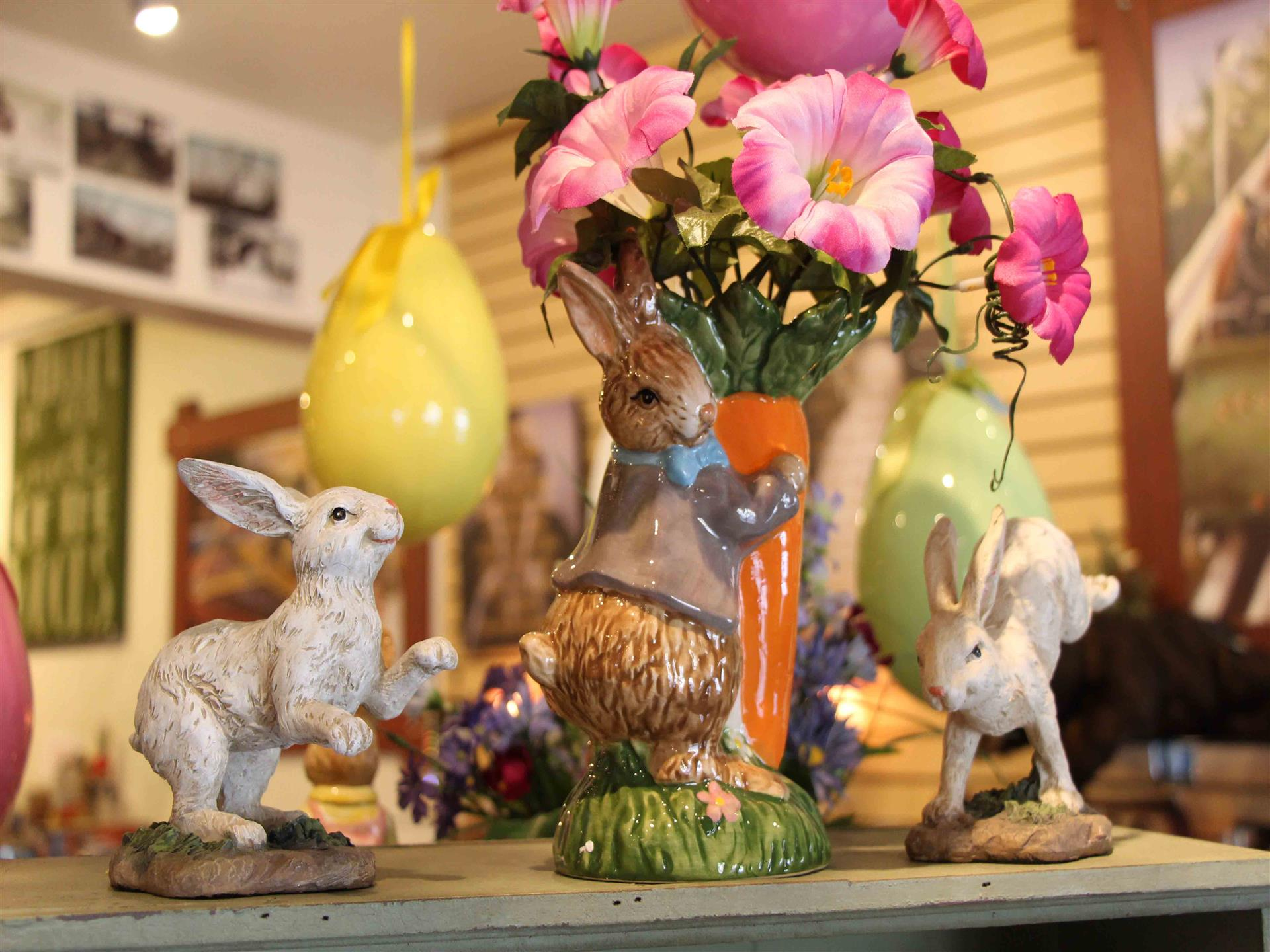 Ceramic bunny figurines with flowers on top of wood shelf