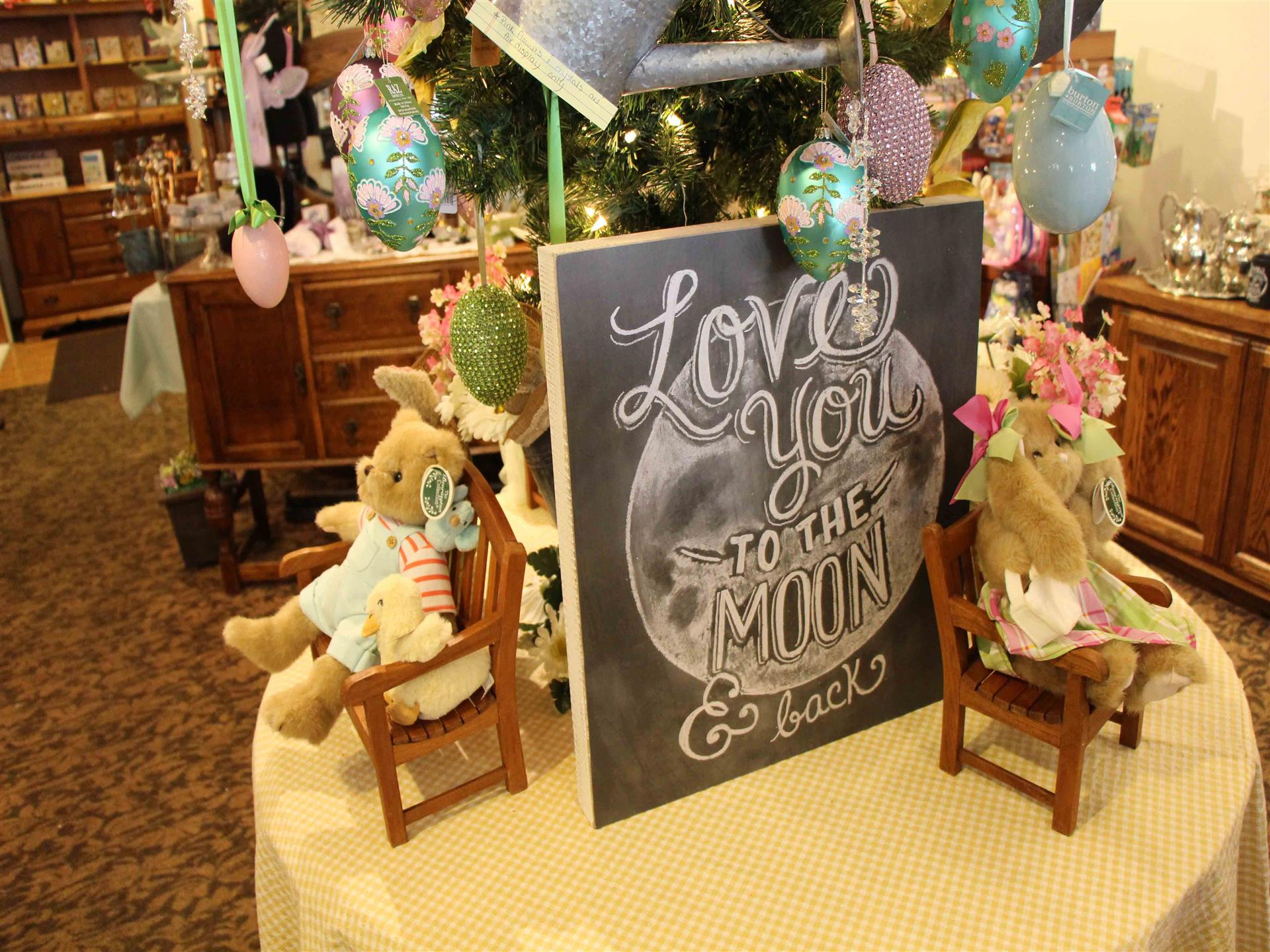 Plush bunnies in miniature chairs next to chalkboard sign that reads Love you to the moon and back
