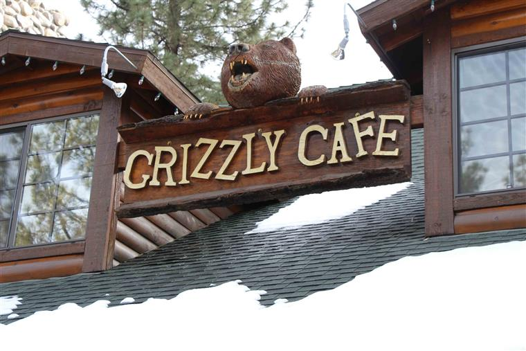 Grizzly cafe sign on roof between dormer windows