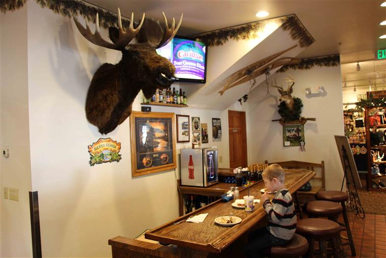 Young boy eating at table inside grizzly cafe under moose head hanging on wall.