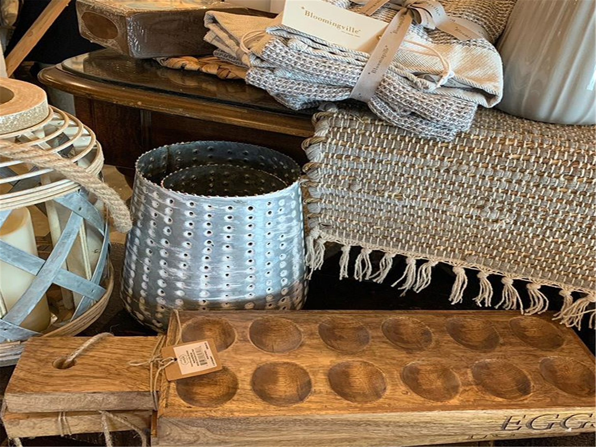 Rustic display of egg tray, woven place mats, lantern and candle holder