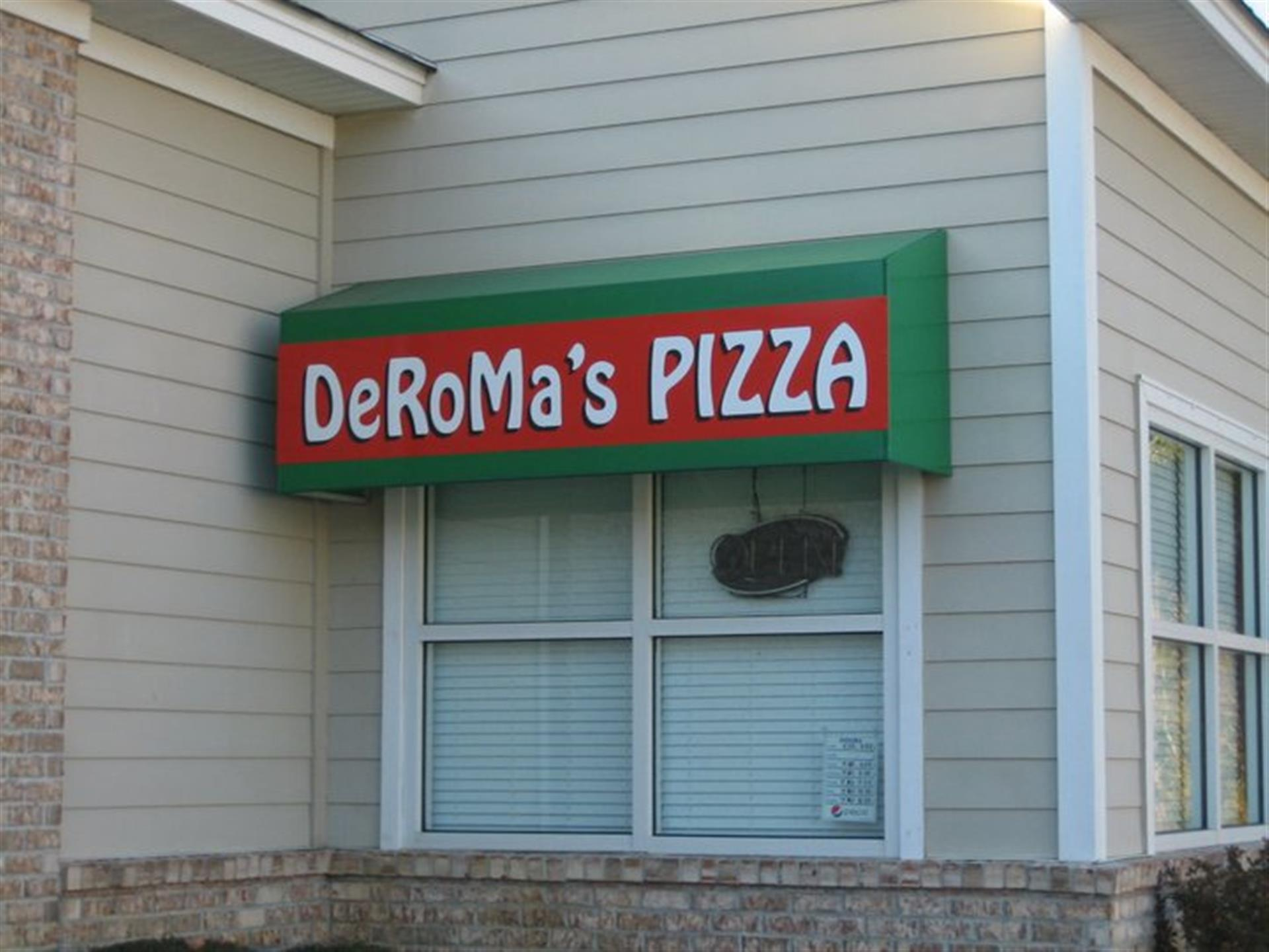 sign on the side of the restaurant that reads deroma's pizza