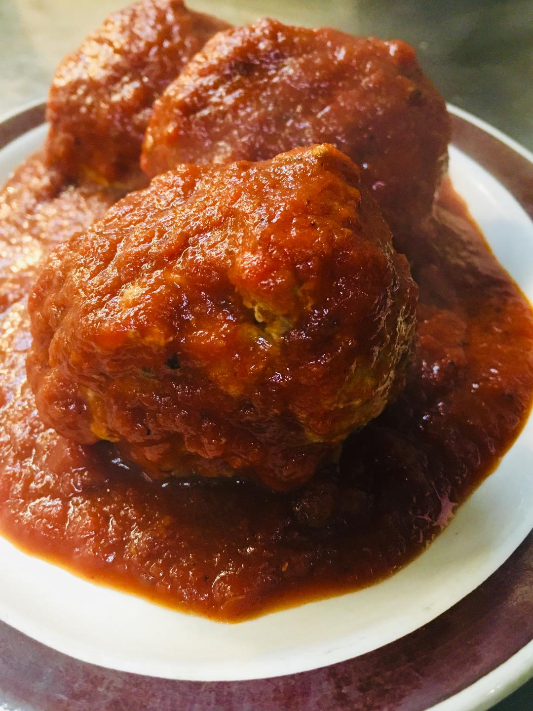 Meatballs on a plate covered in tomato sauce