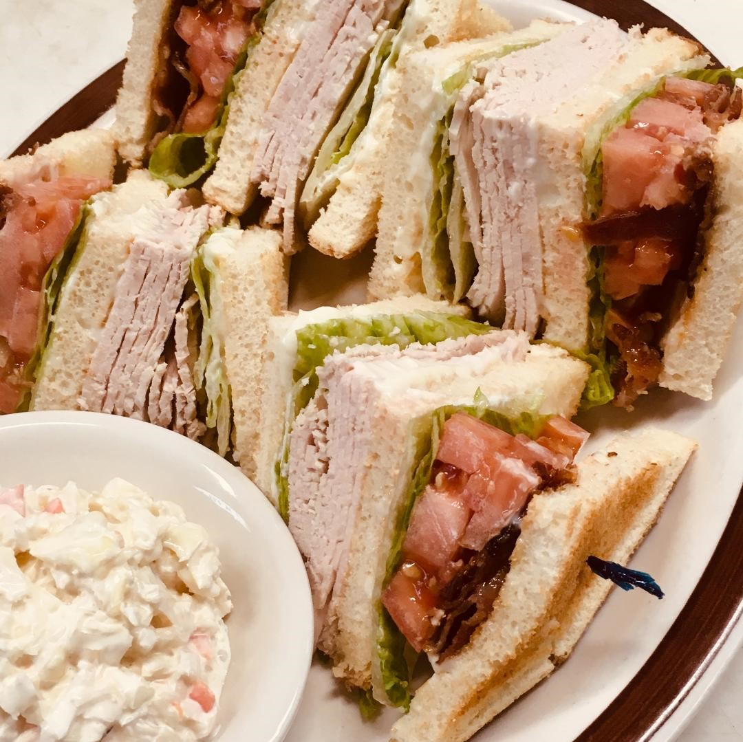 Turkey club sandwiches with lettuce, tomato and bacon and a side of cole slaw