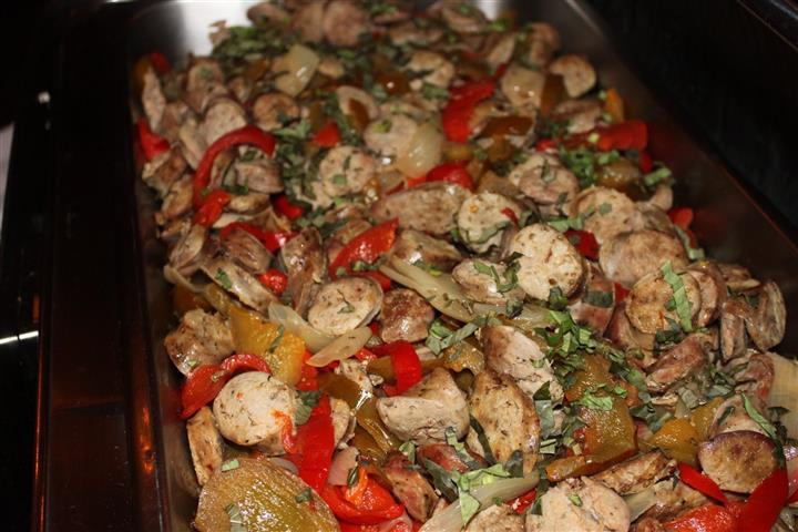 Sausage, peppers, onion in glass pan in the oven