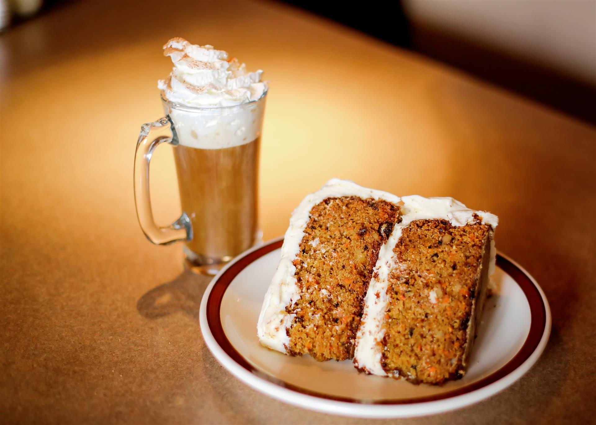 slice of carrot cake on a plate and a coffee next to it topped with whipped cream and cinnamon
