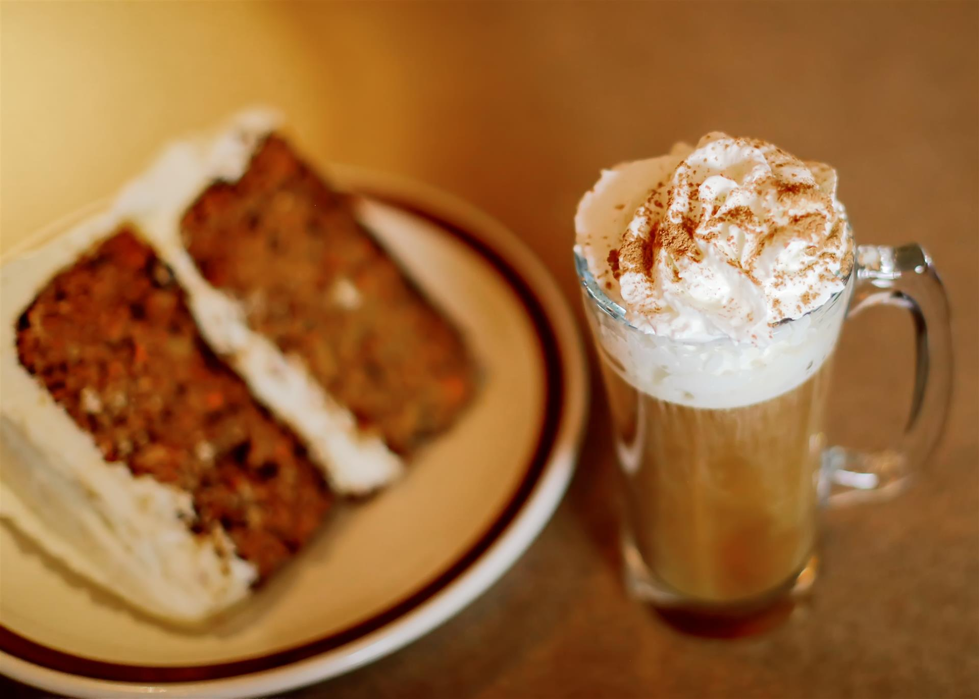 slice of a carrot cake and a coffee with whipped cream and cinnamon on top