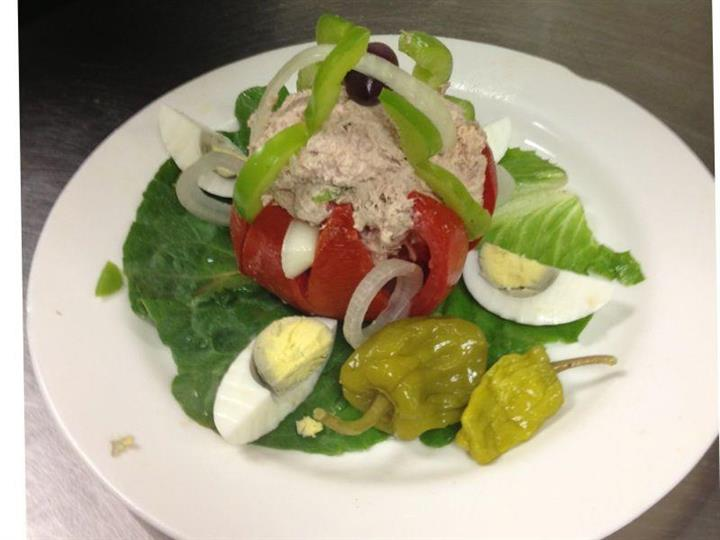 Tuna salad on a plate with green pepeprs, onions, tomato, sweet peppers and hard boiled eggs