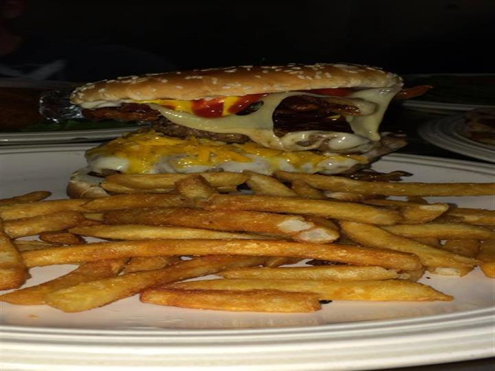 Cheeseburger with onions and ketchup with a side of french fries