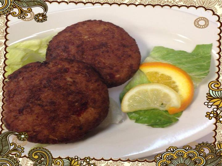 Two homemade crabcakes with two lemon wedges
