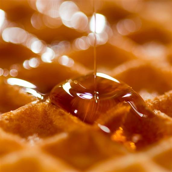 close up of waffle with syrup being poured