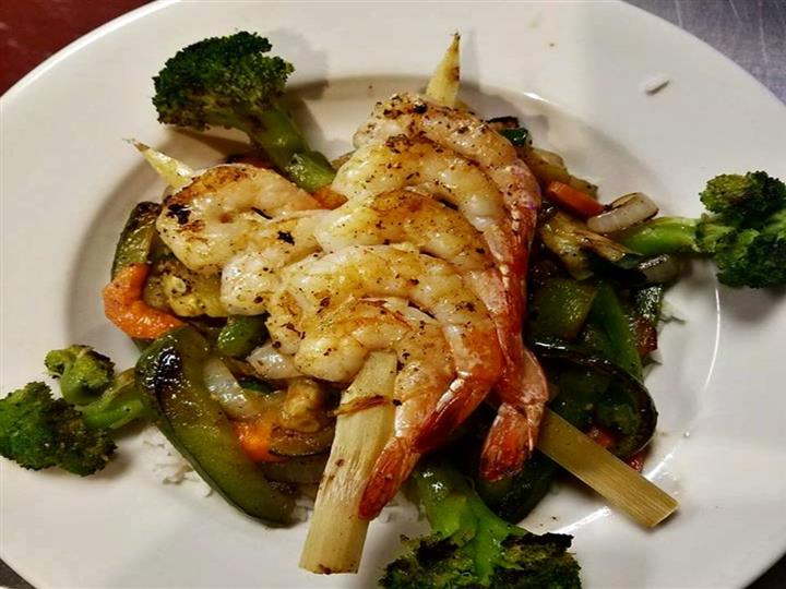 grilled shrimp on top of fresh steamed vegetables