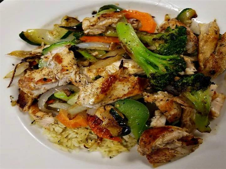 mixed veggie stir fry with broccoli, zucchini, peppers, onions and zucchini served over rice with chicken on top