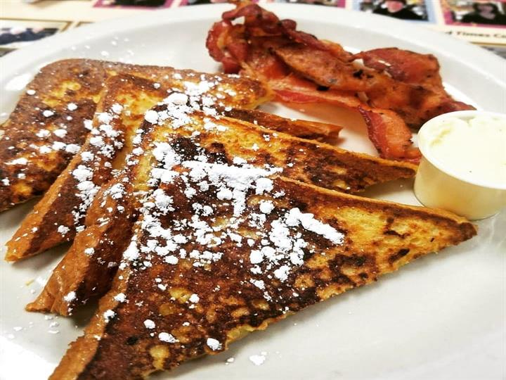 french toast topped with powdered sugar served iwth bacon