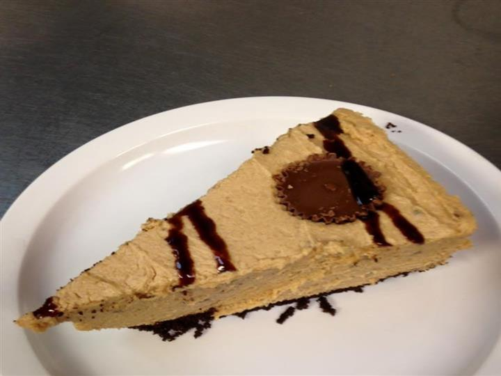 peanutbutter cheesecake drizzled with cholate sause and a peanut butter cup on top