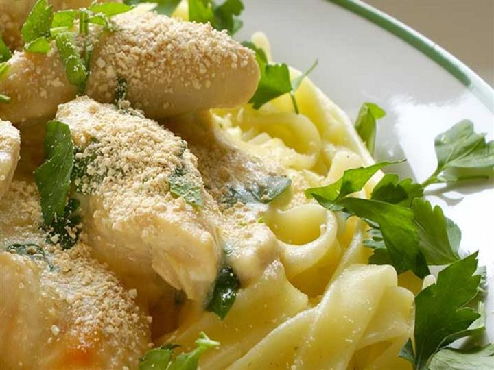 linguine with alreado and chicken breasts garnished with parsley