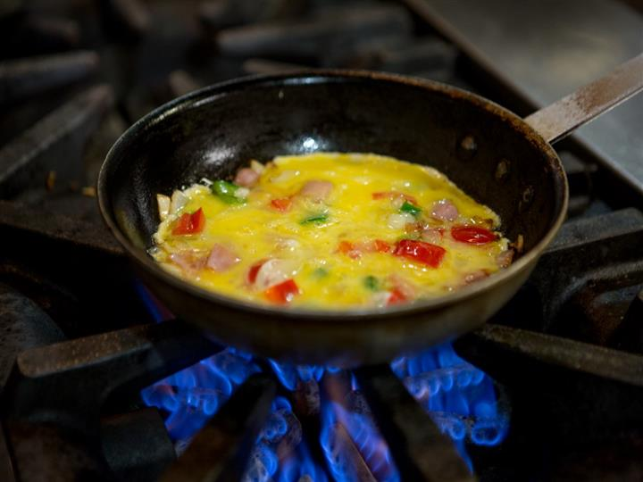 omelette with ham and peppers being cooked in a skillet