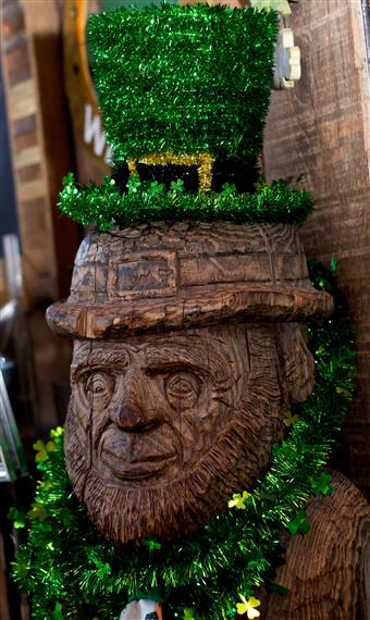 statue of a wooden leprechaun wearing an irish top hat and irish decorations around the neck
