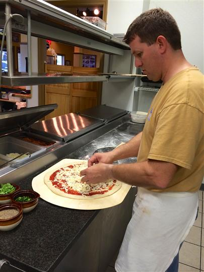 Worker Making Pizza By Putting Toppings on