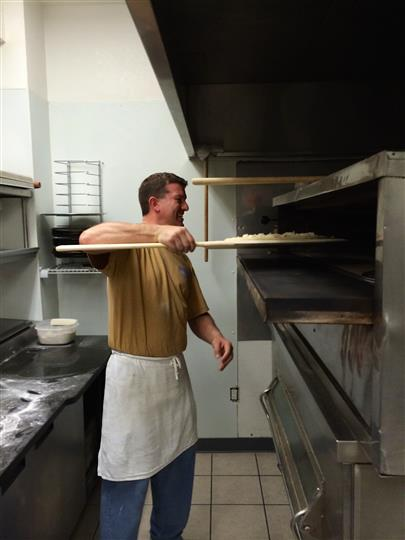 Worker Making Pizza by Putting it in the Oven
