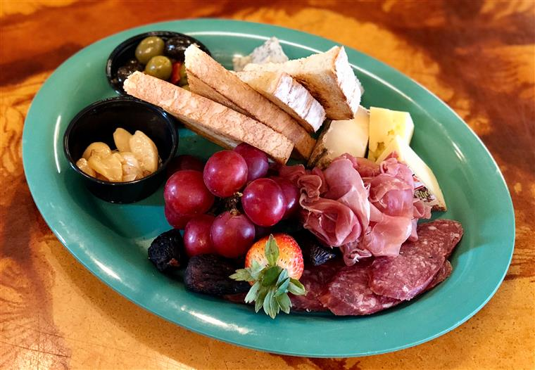 antipasto plastter with toast, grapes, strabwerries, blackberries, cured meats, and olives