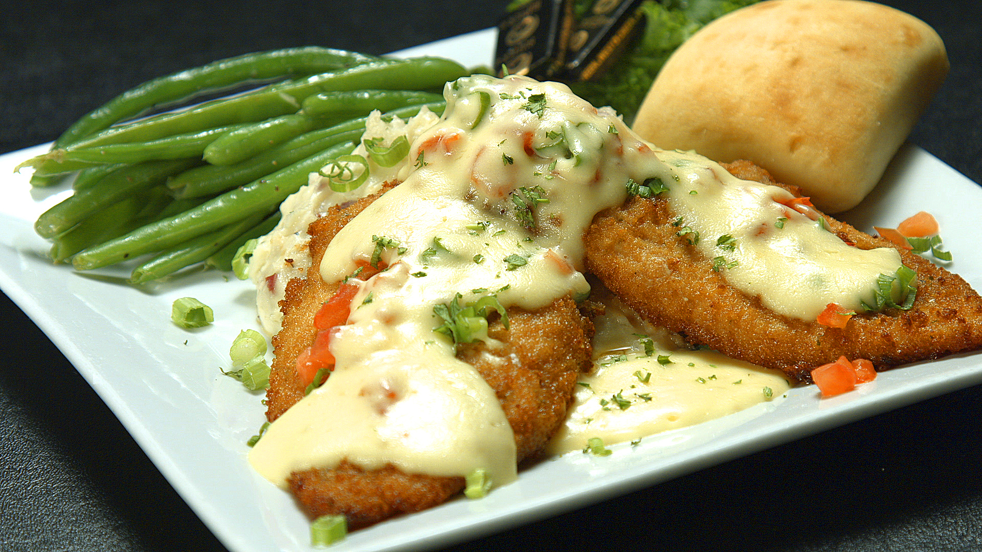 fried fish with a white sauce on top and green beans and bread on the side