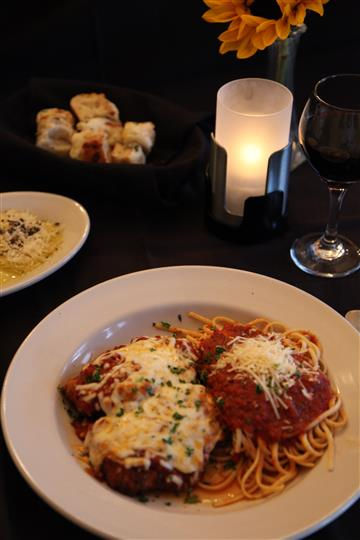 spaghetti and meatballs with a glass of wine