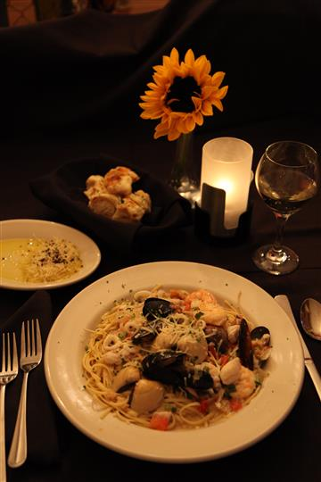 seafood pasta with sauce and a glass of wine