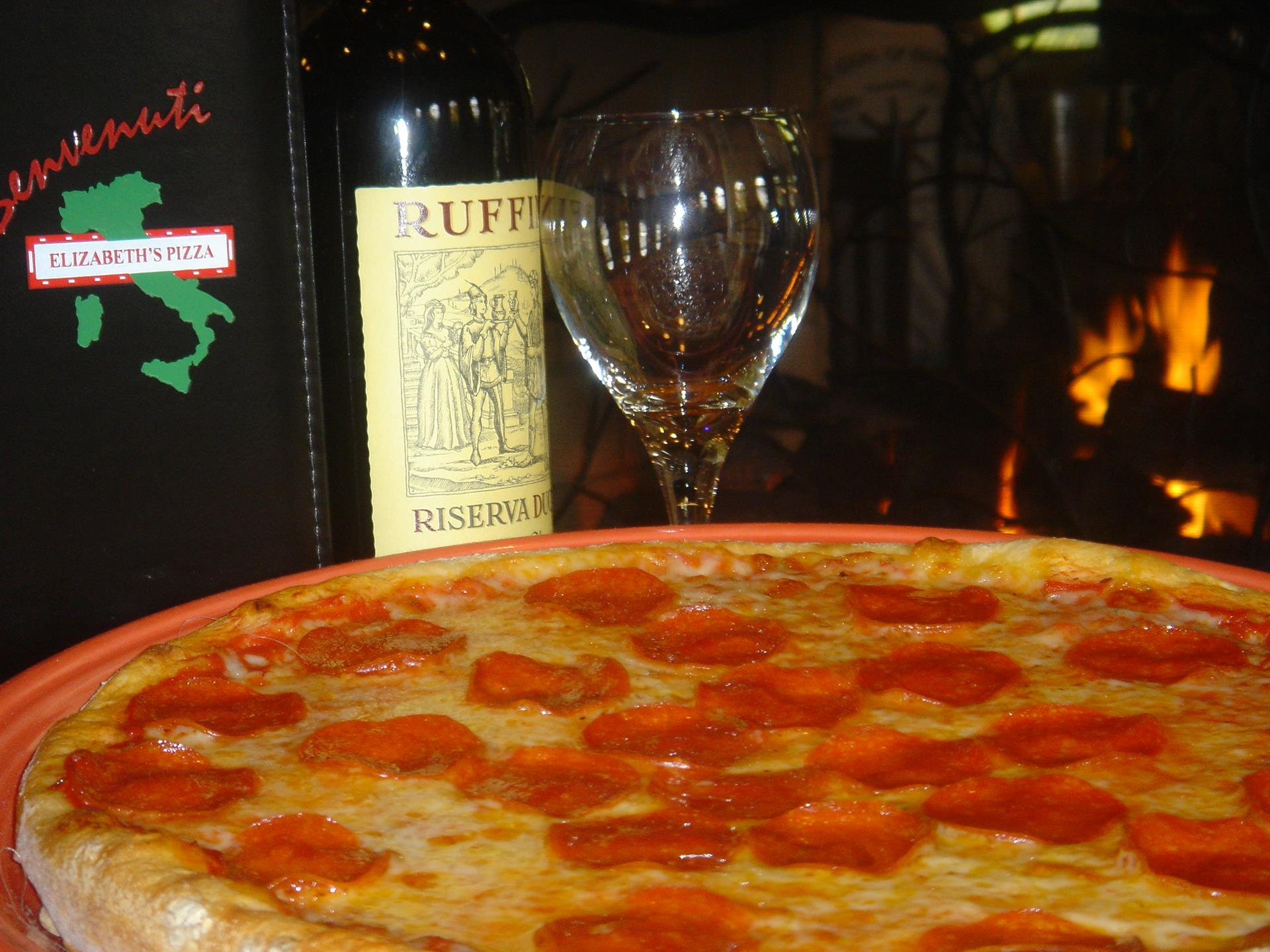 pepperoni pizza with wine bottle and glass in the background