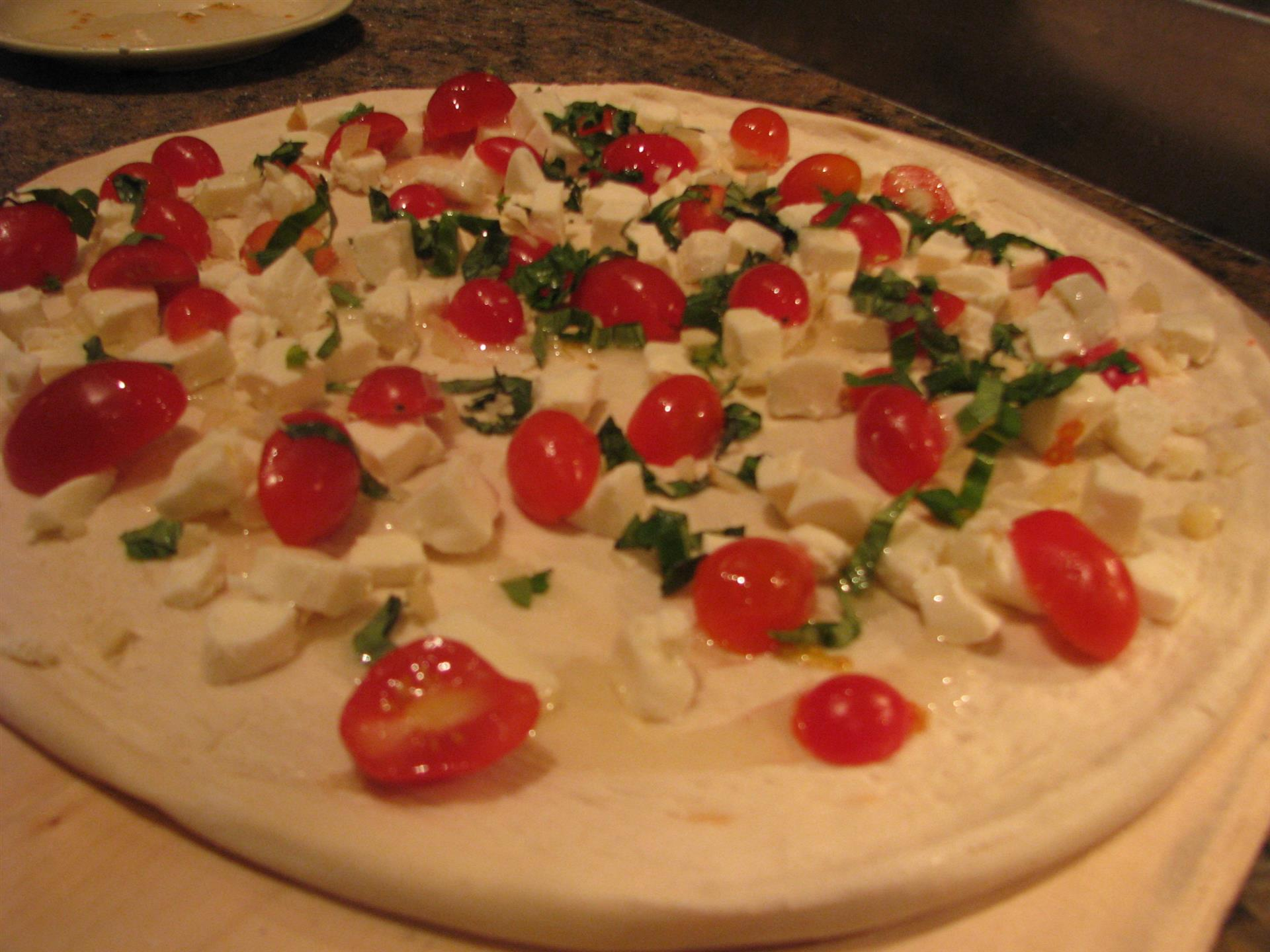 pizza topped with feta cheese and tomatoes