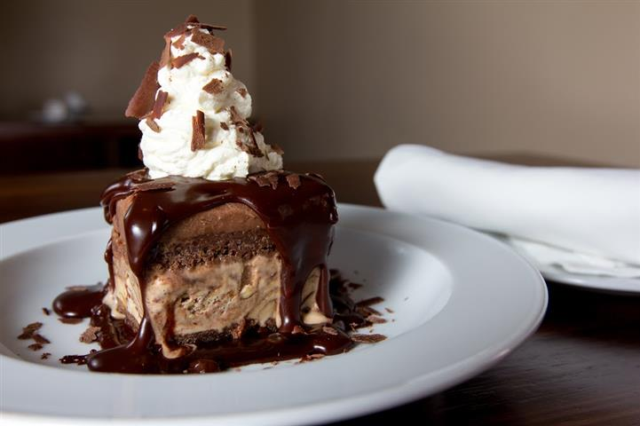 chocolate mousse cake with whipped cream, chocolate fudge and chocolate shavings