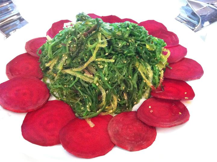 sauteed spinach being displaying for catering with sliced beets around it