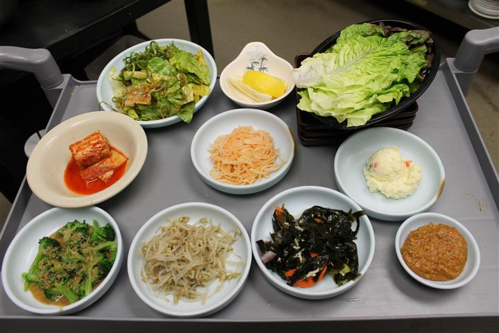 assorted korean dishes being displayed on a platter