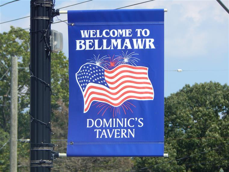 flag hanging from a street post that says welcome to bellmawr dominic's tavern