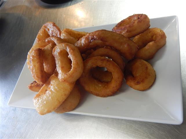 plate of fried onions rings on a counter