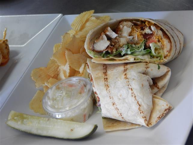 grilled chicken wrap with lettuce, tomatoes and side of chips with coleslaw and a pickle spear